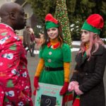 Isla (played by Isabella Gomez) and Kat (played by Laura Marano) talk to their ambitious boss Mr. Mujiza (played by Garfield Wilson) at Santa Land.